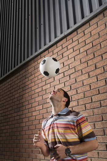 Young man bouncing ball off head against brick wall