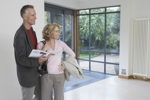 Happy couple with brochure observing new property