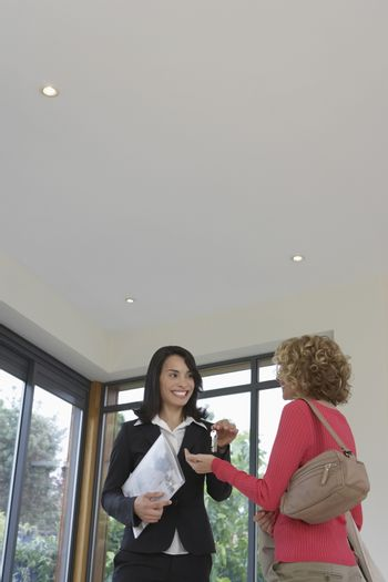 Real estate agent handing woman keys in new property