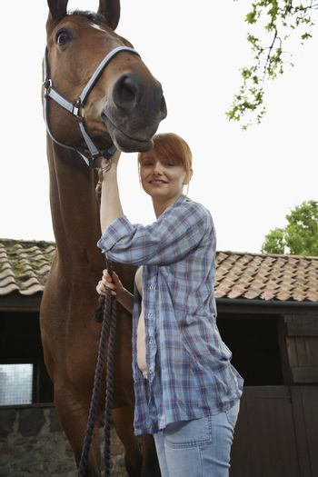 Portrait of a red haired young woman with horse outside stable