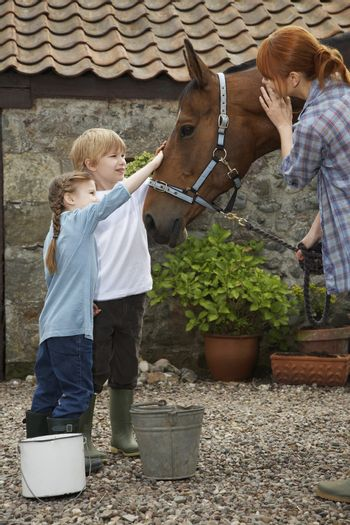 Side view of children and mother stroking horse outside stable