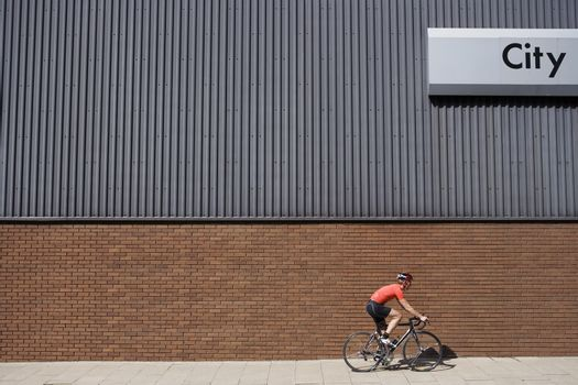 Side view of a man cycling past building with 'City' written on side