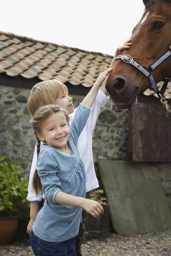 Smiling girl and boy stroking horse outside stable