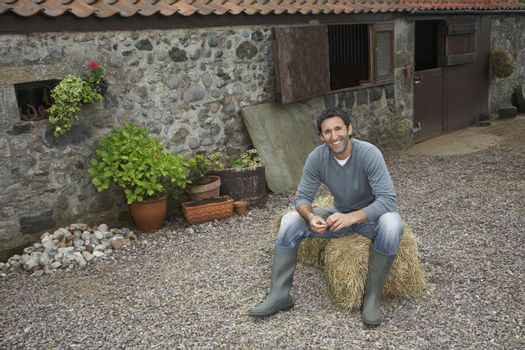 Portrait of a smiling man sitting on haybale outside stable