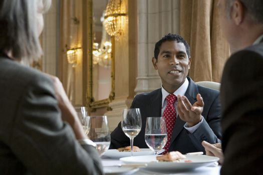 Mixed race businessman in discussion with colleagues at restaurant table