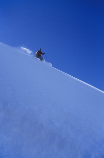 Person skiing down slope side view