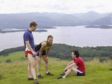 Three joggers relaxing in countryside