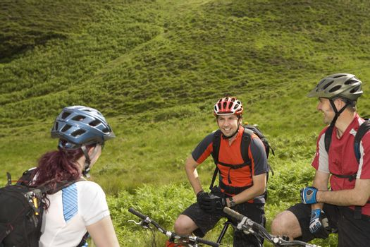 Happy three cyclists with bikes against lush landscape