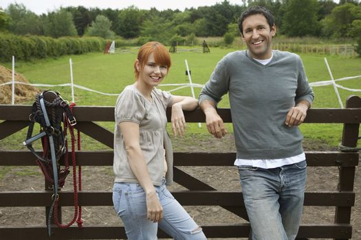 Portrait of a smiling couple against fence in paddock
