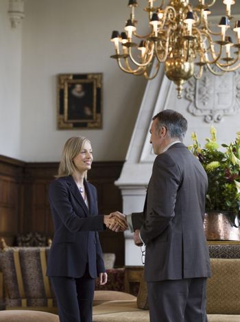 Side view of a businesswoman and man shaking hands under chandelier