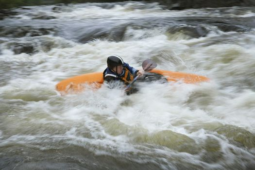 Side view of a man kayaking in rough river