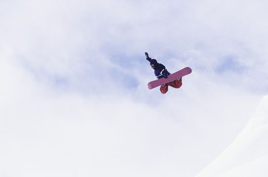 Person on snowboard jumping view from below
