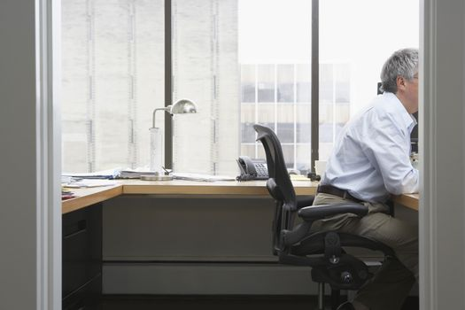 Side view of a businessman working at desk in office