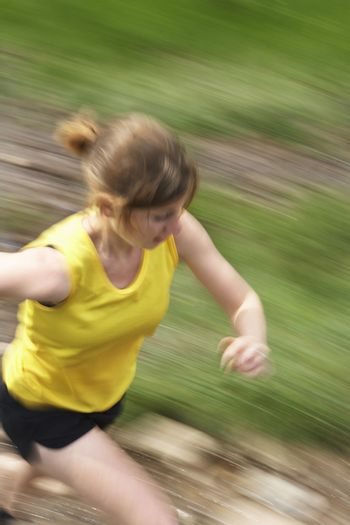 Elevated view of a woman running on track