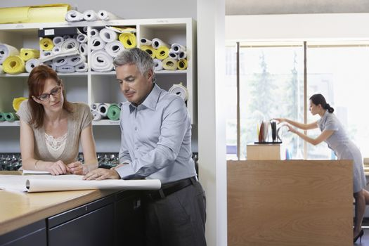 Businessman and woman studying paperwork in office