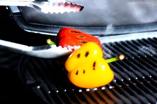 Bell peppers on a grill and tongs