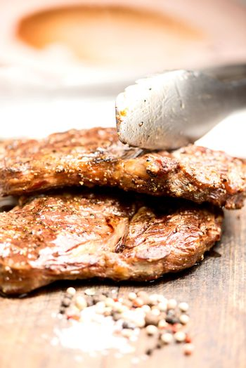 grilled steaks on an old wooden board with tongs
