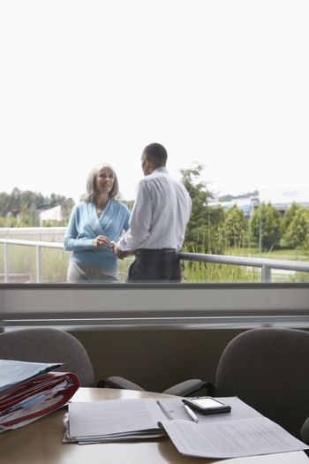 View through window of business couple talking on terrace