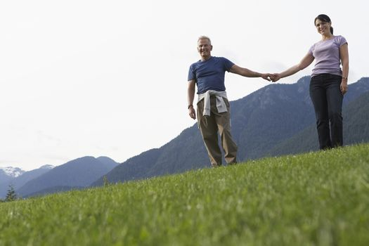 Portarit of couple holding hands mountain range in background