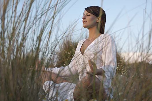 Young woman meditating on sand dunes