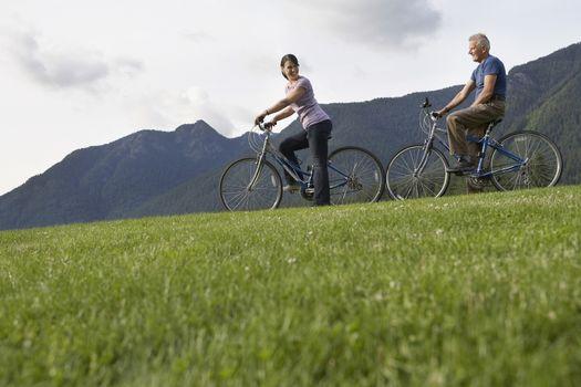 Man and woman biking mountain range in background