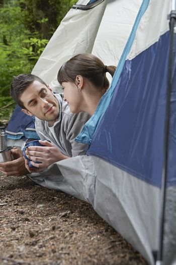 Couple with drinks lying in tent entrance