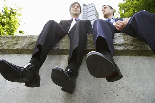 Low angle view of two businessmen sitting side by side on wall