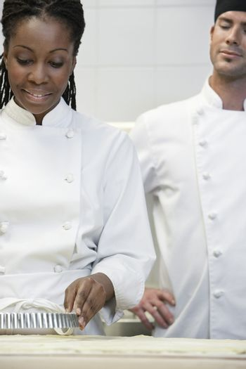 Male chef watching female colleague prepare food in the kitchen