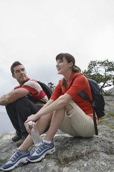 Couple sitting on rocks at ocean