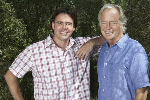 Portrait of a smiling father and adult son in the garden