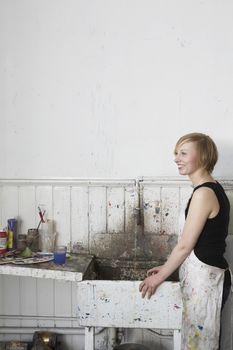 Artist standing by sink in studio