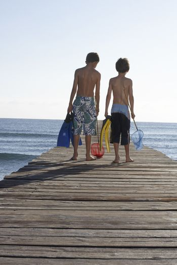 Full length rear view of two shirtless boys walking on jetty with fishing nets and swim fins