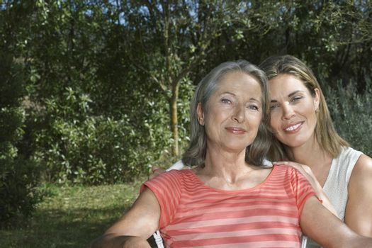 Portrait of smiling mother with adult daughter in the garden