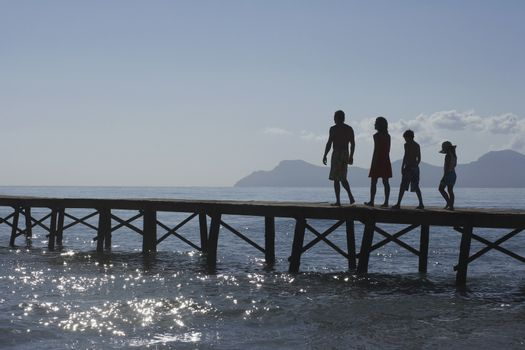 Full length of silhouetted parents and two children walking on jetty