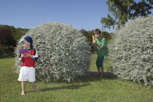 Two young boys playing with water pistols among bushes