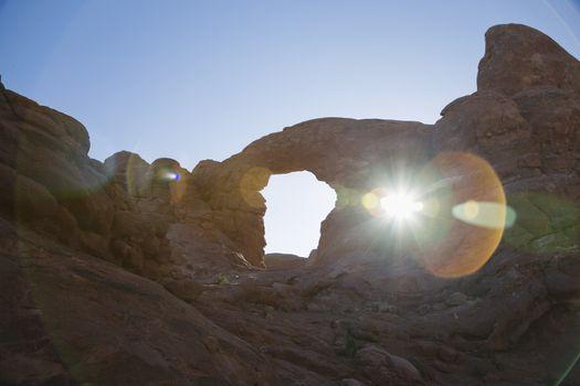 USA sun shining through rock formation in desert