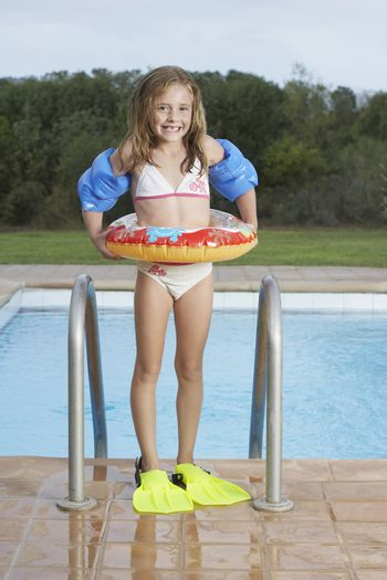 Full length portrait of a smiling girl with inflatable ring and swim fins against pool