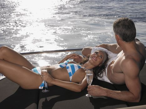 Couple with champagne flutes relaxing on yacht's edge