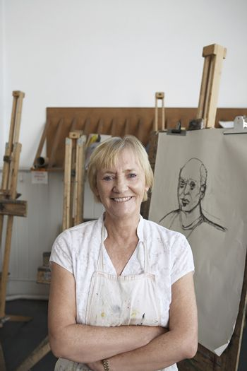 Portrait of a smiling mature female artist standing by artwork in studio