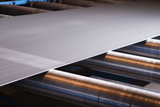 Continuous sheet of metallic material being fed through machine