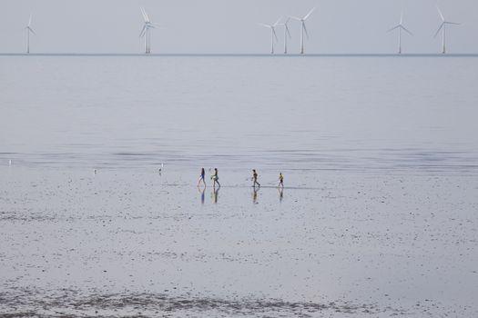 People running on beach wind farm in distance