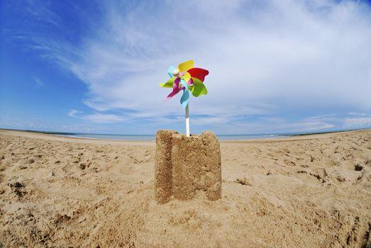 Sand castle with pinwheel on beach
