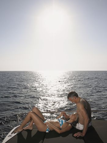 Affectionate couple relaxing at the edge of yacht by sea
