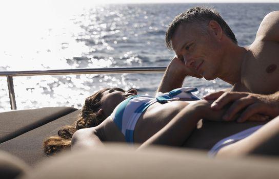 Romantic couple sunbathing on yacht's edge during summer