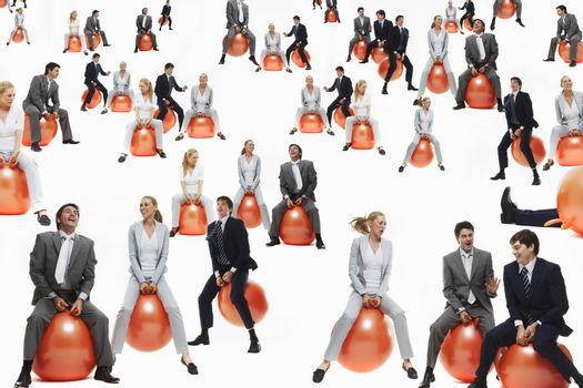 Businesspeople bouncing on inflatable balls isolated over white background