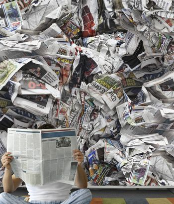 Man reading newspaper against pile of papers