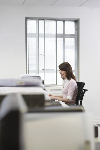 Young businesswoman working on desktop pc in office