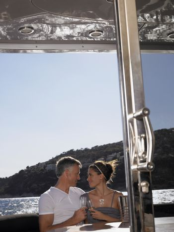 Affectionate couple looking at each other while having champagne on yacht