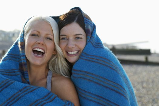 Two women laughing covered under blanket portrait