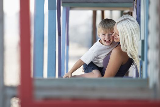 Cheerful mother and son playing at porch